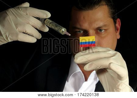 Young Businessman Gives A Financial Injection To Colombian Flag Isolated On Black Background