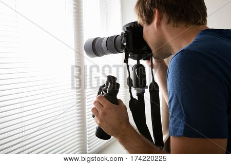 Young Male Holding Camera Photographing Through Blinds At Home