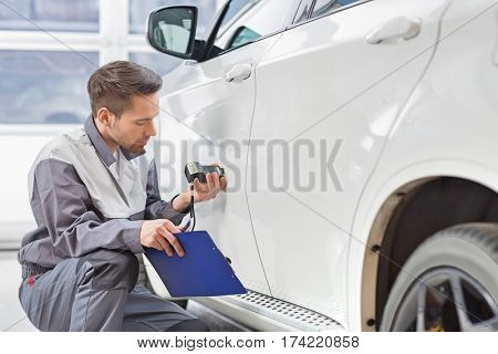 Male repair worker examining car paint with equipment in repair shop