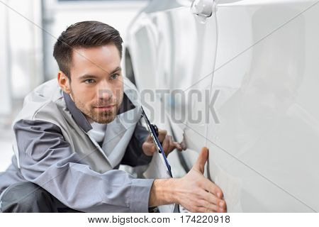 Young automobile mechanic examining car in repair store