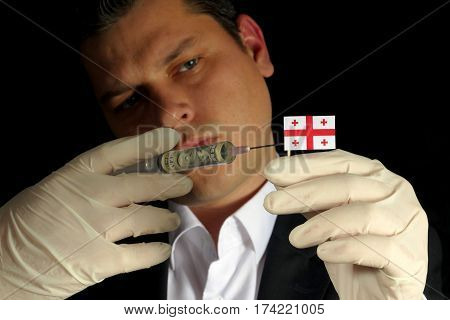 Young Businessman Gives A Financial Injection To Georgian Flag Isolated On Black Background