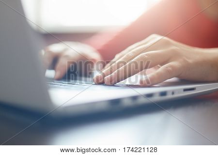 Close-up portrait of woman's hands typing on laptop sitting at the table. Female businesswoman working on-line via laptop computer sitting in front open net-book. Selective focus on fingers