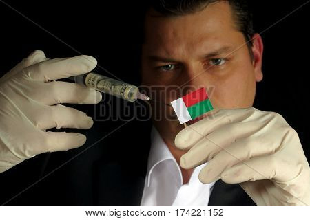 Young Businessman Gives A Financial Injection To Malagasy Flag Isolated On Black Background