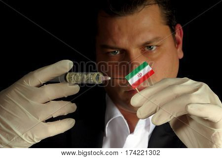 Young Businessman Gives A Financial Injection To Iranian Flag Isolated On Black Background