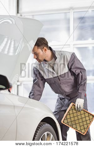 Young automobile mechanic examining car in automobile shop