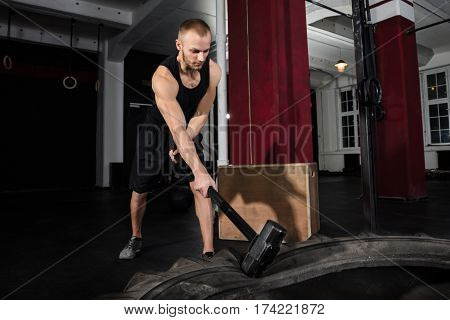 Man Hitting A Tractor Tire With Hammer In A Gym During Intense Training