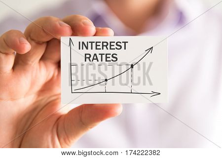 Businessman Holding A Card With Interest Rates Rising Arrow And Chart