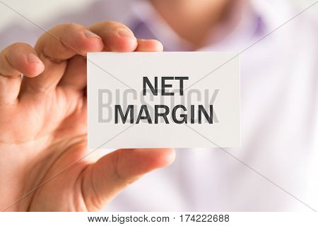 Businessman Holding A Card With Net Margin Message