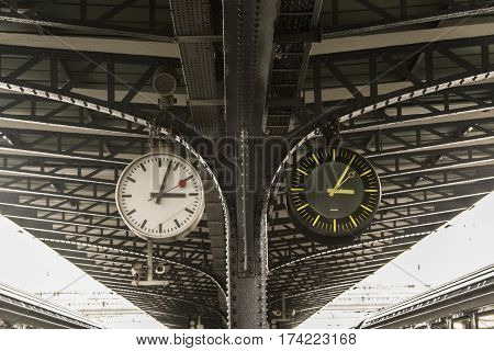 Old and new clock next to each other on the platform of the train station Picture of an old and a new clock next to each other indicating the same time