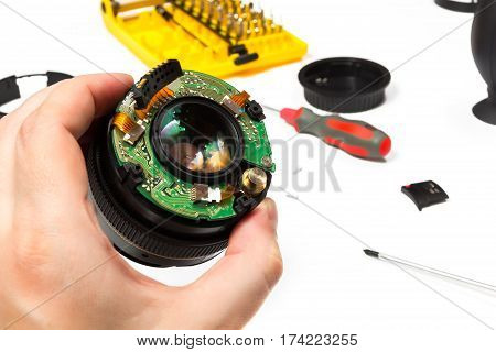 Left human hand holding half-disassembled camera lens during repair on bright white background with selective focus.