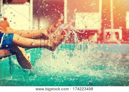 Boys legs splashing water in pool summer holiday vintage