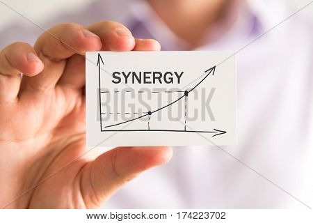 Businessman Holding A Card With Synergy Rising Arrow And Chart