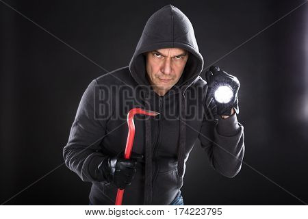 Portrait Of A Male Thief Holding Flashlight And A Crowbar On Black Background