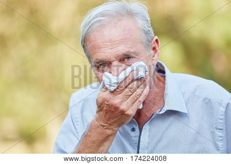 Senior man with hay fever using a tissue in the nature