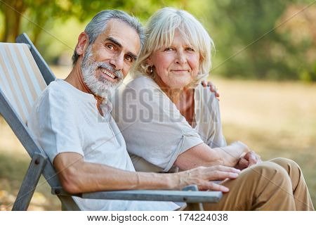 Senior couple sitting happily on a deck chair in the nature