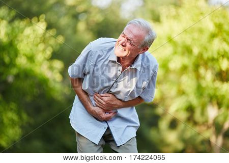 Old man with stomach ache toching his stomach in the nature