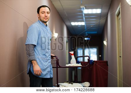Man cleaning hotel hall wearing blue coat.