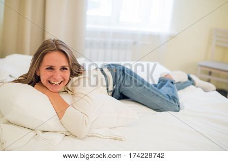 Smiling thoughtful pretty woman lying in bed at home.
