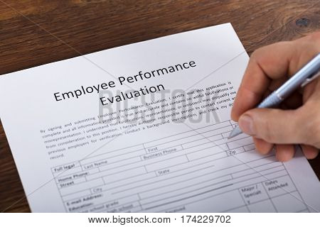 High Angle View Of A Person Filling A Performance Evaluation Form Of Employee
