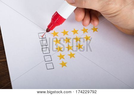 Person Giving Best Rating On Paper Using Red Marker