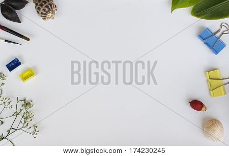 White background with colorful objects. Blank paper banner template with floral decor and text place. White card for lettering or painting mockup. Art supplies flat lay composition with white canvas