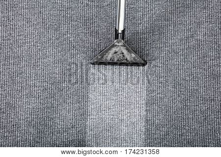 Close-up Of Vacuum Cleaner Cleaning Dirt On Carpet