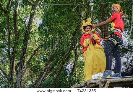 Labuan,Malaysia-Feb 12,2017:Happy girl in teddy bear costume enjoying on a flying fox in Labuan,Malaysia.There will be more ziplines in Malaysia,especially when there have so much natural resources & rainforest.