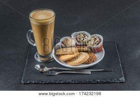 aromatic coffee latte with three buttered muffins and petit fours on a white saucer with a spoon and forks the whole on a black stone plate sweet set
