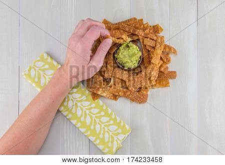 Left Hand Dips Chip in Guacamole from above view