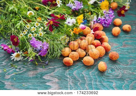 Bouquet of fresh summer flowers on the blue wooden grunge desk with apricot fruits. Background in vintage hipster eco rustic style with copy space