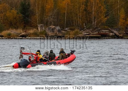 Red inflatable boat with fishermans moving at speed