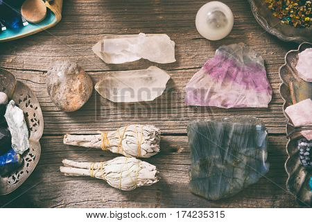 Natural gemstones, white sage and incense on wooden board