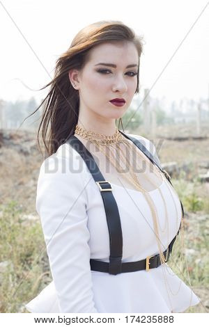 Beautiful Young Girl In A White Suit With A Leather Harness.