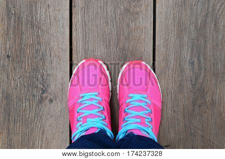 Woman Leg With Pink Sport Shoe On Brown Wood Slat Floor