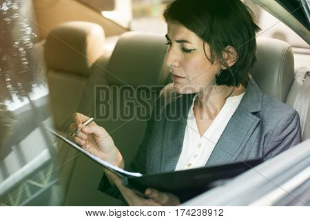 Businesswoman signing contract on backseat of the car