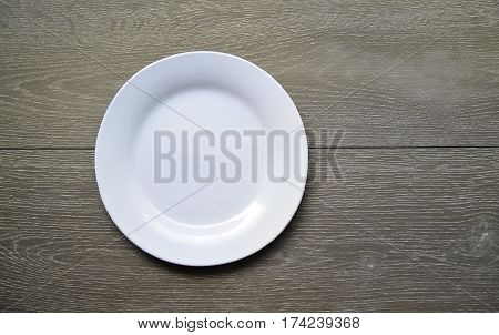 Empty white plate on a wooden background