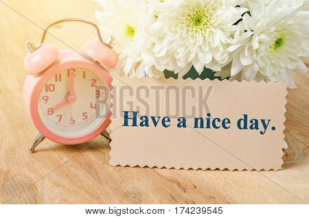 Have a nice day card and vintage pink alarm clock with white flower on wooden background.