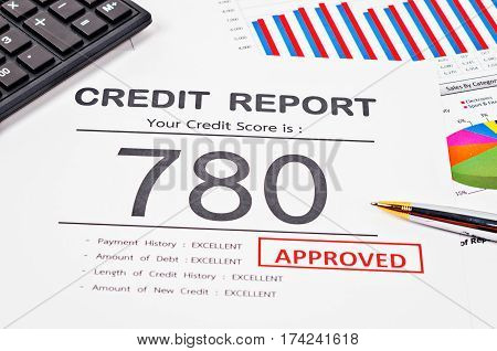 Credit score report and approved with pen and calculator on business report document.