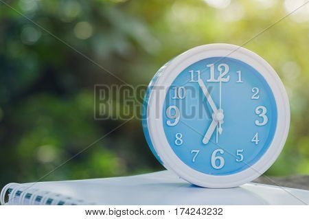 Blue alarm clock on notebook with nature background close up blue alarm clock and notebook