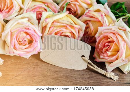 Pink rose with empty paper tag on wooden background Ready for your text.