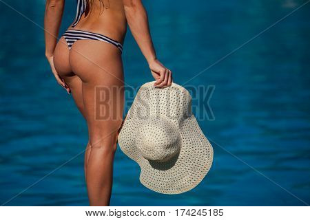 It is close up fashion image of gorgeous woman with perfect body and butt holding hat, posing near luxury pool wearing pretty bikini