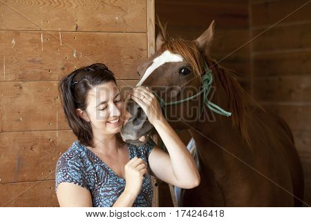 Woman smiling while holding horse in barn