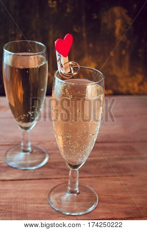 wine glasses with white sparkling wine and golden wedding rings on a wooden table against black and gold wall