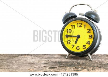 Closeup black and yellow alarm clock for decorate show a quarter to seven p.m. or 6:45 a.m. on old brown wood desk isolated on white background with copy space