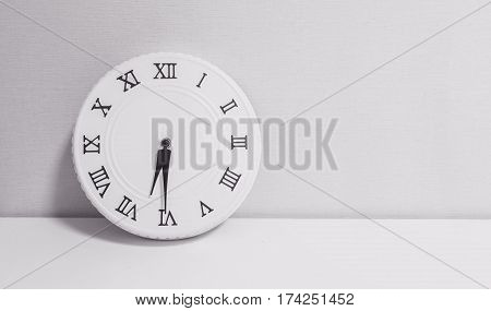 Closeup white clock for decorate show half past six or 6:30 a.m. on white wood desk and wallpaper textured background in black and white tone with copy space