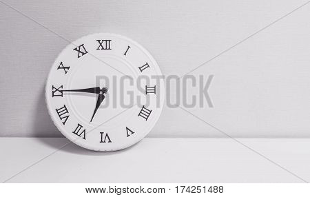 Closeup white clock for decorate show a quarter to seven or 6:45 a.m. on white wood desk and wallpaper textured background in black and white tone with copy space