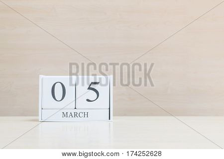 Closeup surface white wooden calendar with black 5 march word on blurred brown wood desk and wood wall textured background with copy space selective focus at the calendar