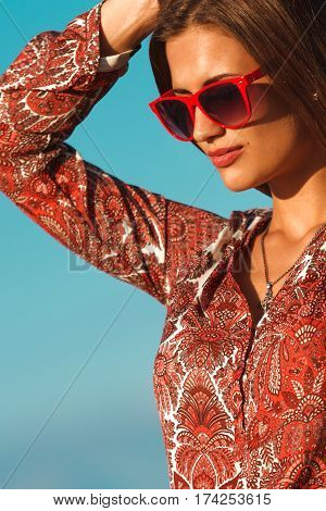Fashion woman portrait posing in red sunglasses