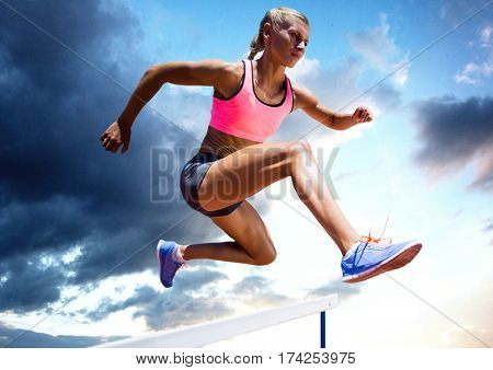 Composite image of athlete jumping over a hurdle against sky in background