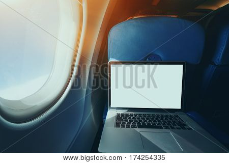 Wide angle shooting of contemporary laptop with blank screen on the blue table of airplane seat mock up of modern portable computer next to illuminator of flying plane with sunny day outside
